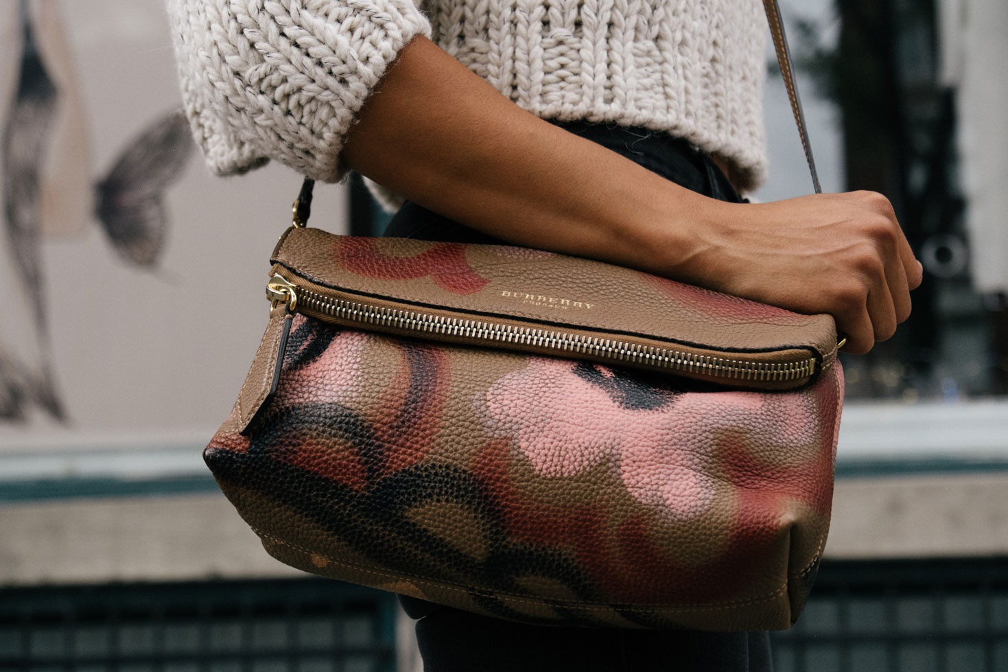 A woman wearing a white knit sweater carrying a signature Burberry bag in hand.