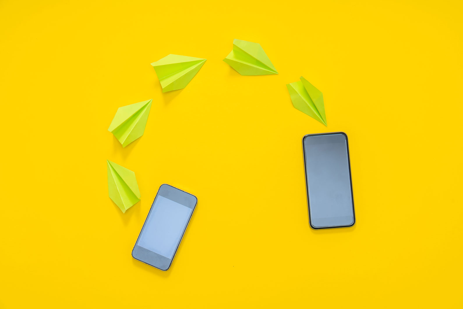 Two mobiles are placed on a yellow background and origami planes are kept between the two to show sharing of files.