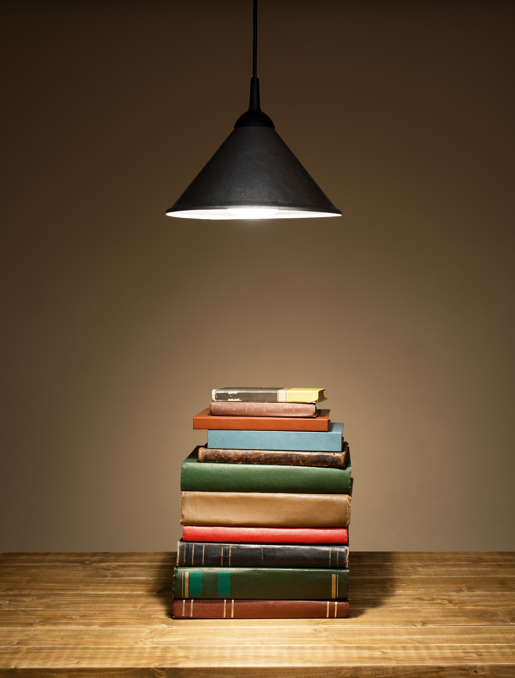 A pile of books are stacked on a wooden table.