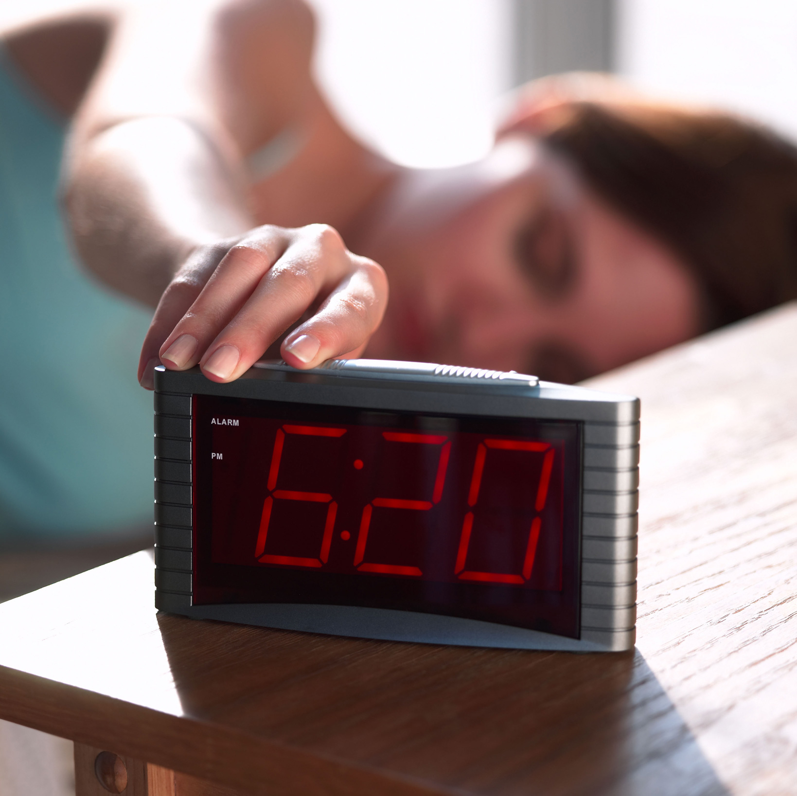 Woman hitting the snooze button on the alarm clock