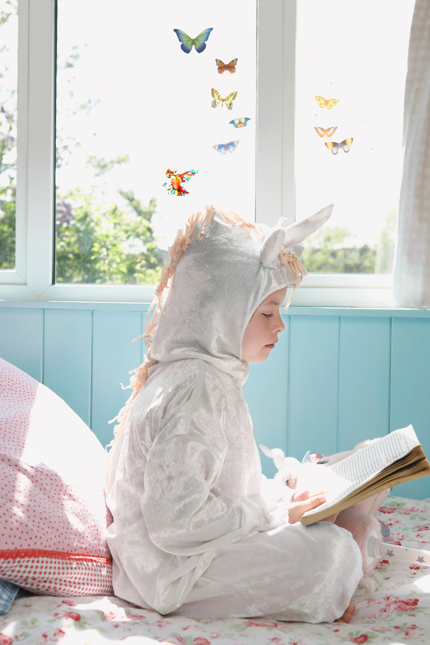 A cute young girl sitting on her bed in unicorn themed costume reading a storybook.